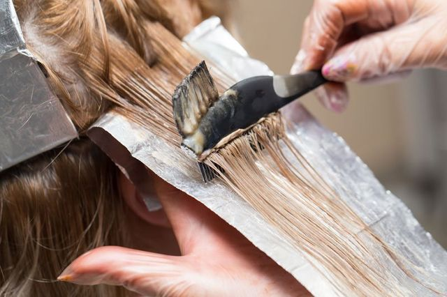 Parrucchiere applica tinta per capelli a Triggiano