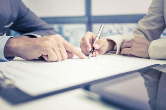 Una persona indicando all'altra dove deve firmare