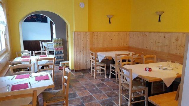 Interno del bar Pizzeria da Gennaro, a Malborghetto Valbruna con liquori esposti, macchina del caffè e vetrina di salumi e formaggi