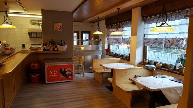 Interno del Bar Pizzeria da Gennaro con arredamenti in legno, parquet in legno, tavoli con panche e lampade a sospensione