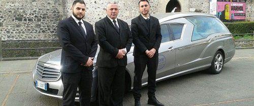 tre uomini in giacca e cravatta vicino a un carro funebre