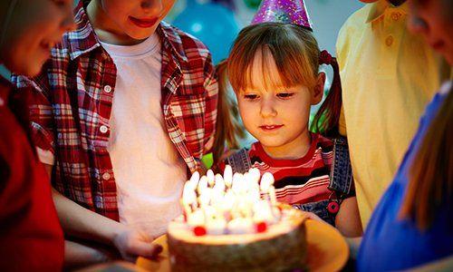 Dei bambini con una torta in mano con delle candele accese