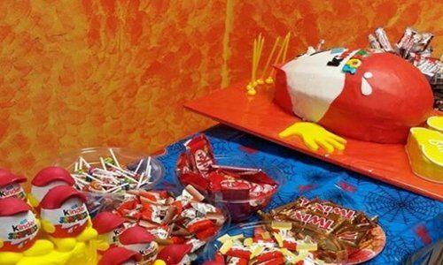 Un tavolo con una torta a forma di un cioccolato Kinder e accanto altri cioccolatini