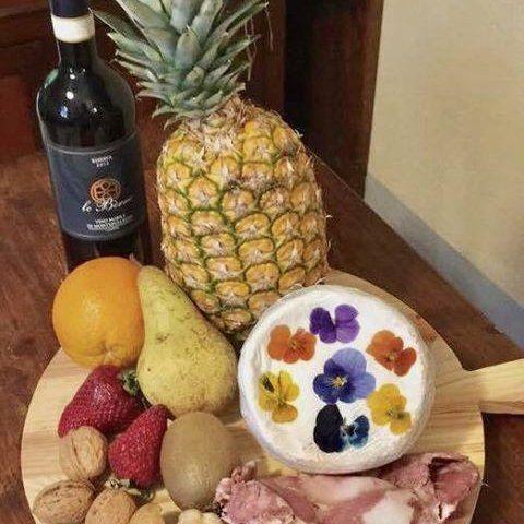 bottiglia di vino accanto a un ananas, frutta secca, un'arancia e una pera