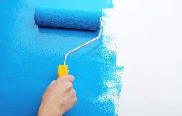 una mano con un rullo con della vernice di color blu