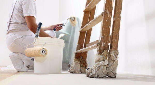 un imbianchino mentre dipinge un muro