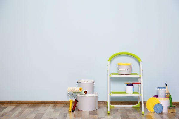 una stanza con un muro verniciato in color azzurro e una scaletta con dei barattoli di vernice
