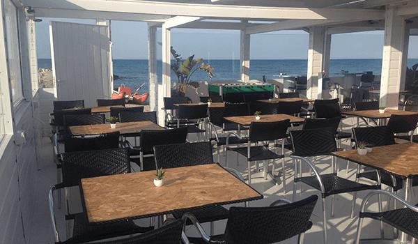 interno di un locale con tavoli marroni e sedie nere e vista attraverso i vetri del mare