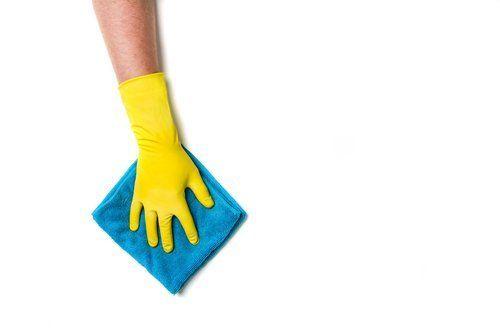 mano con guanto giallo che pulisce con un asciugamano azzurro