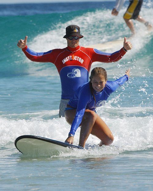 Young girl learning to surf in water