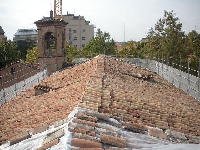 ristrutturazione di un tetto di una chiesa e sulla sinista si vede il campanile