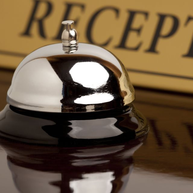 A reception bell on a brown wooden counter