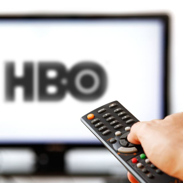 A hand controlling a TV remote with in the background a TV playing HBO