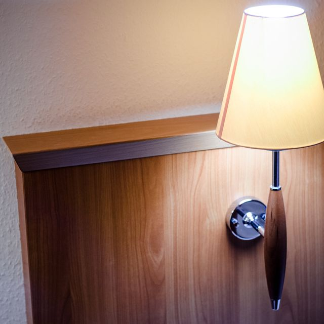 The headrest of a bed in a hotel room along with a nightlight