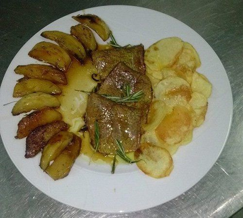 piatto di carne con patate al forno