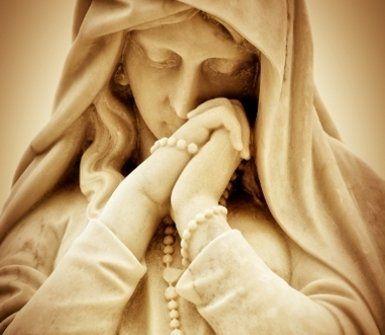 statua della madonna mentre prega con il rosario in mano