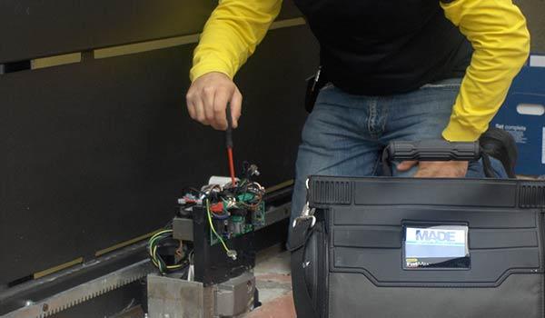 un elettricista con una maglietta gialla e nera chinato a terra con in mano un cacciavite che sta testando la presenza di corrente in un quadro elettrico di un cancello