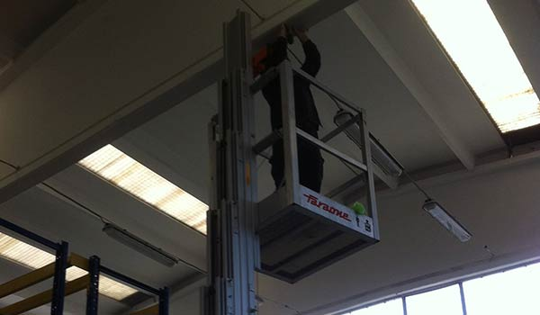 un uomo al lavoro su un impianto elettrico sopra ad una piattaforma all'interno di un magazzino