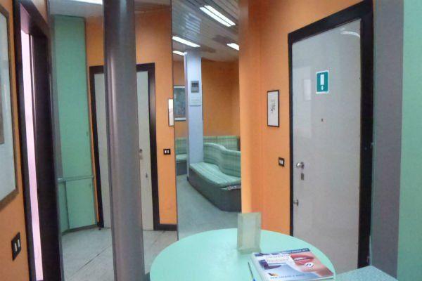 interno dello studio dentistico con pareti verde e arancio e mobili verdi