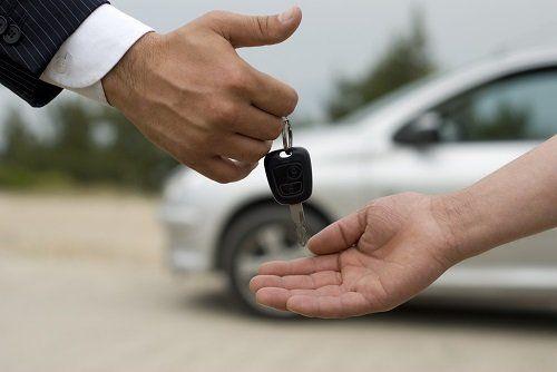 un uomo passa le chiavi dell'auto a un altro uomo