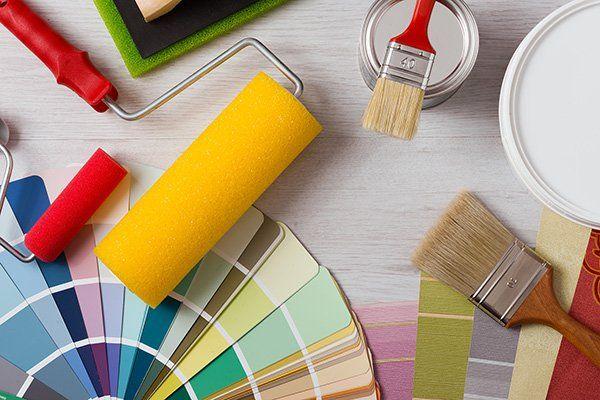 Tavolo da lavoro di pittore e decoratore con campioni di colore, rullo di pittura e spazzole