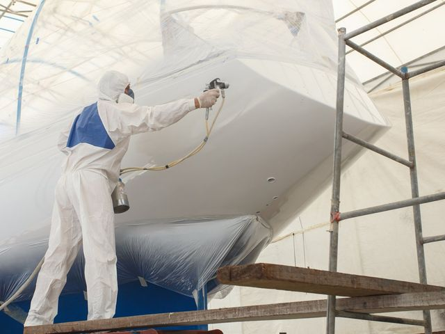 Man spraying a boat in epoxy coating