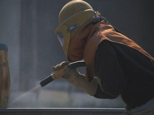 Man grit blasting metal work