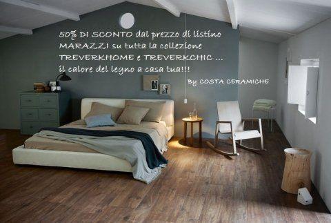 Camera da letto con pavimento in legno,sedia a dondolo e soffitto inclinato