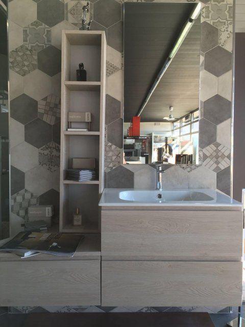 Bagno con mobili in legno e originali piastrelle esagonali di diverso colore e progettazione