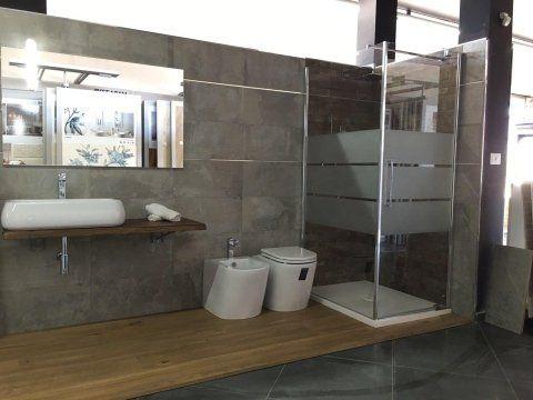 Bagno con pavimento e mobili di legno, box doccia e grande specchio su lavabo rettangolare