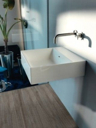 Bagno con pavimento in legno e lavabo incassato nella parete