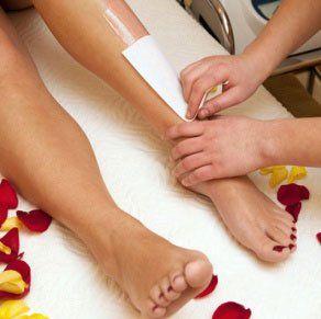 un'estetista mentre utilizza una striscia epilatoria sulle gambe di una donna