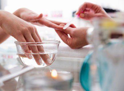 un'estetista mentre fa un manicure a una donna