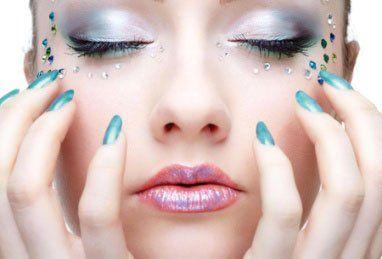 Il viso di una donna e delle mani con uno smalto verde smeraldo