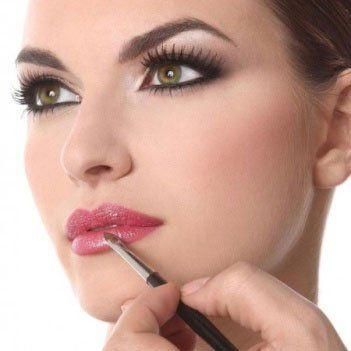Il viso di una donna mentre si applica del rossetto