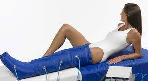 Una donna sdraiata con la gamba dentro un tutore blu con dei cavi collegati