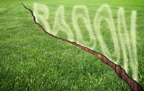 A green mowed lawn with a diagonal crack with radon gas escaping