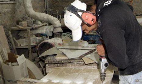 un operaio con un cappellino e un trapano mentre sta forando un asse di legno