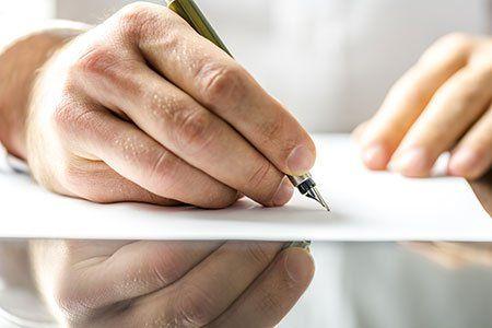 una mano con una penna che scrive su un foglio