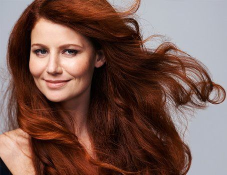 female model with long, flowing auburn hair