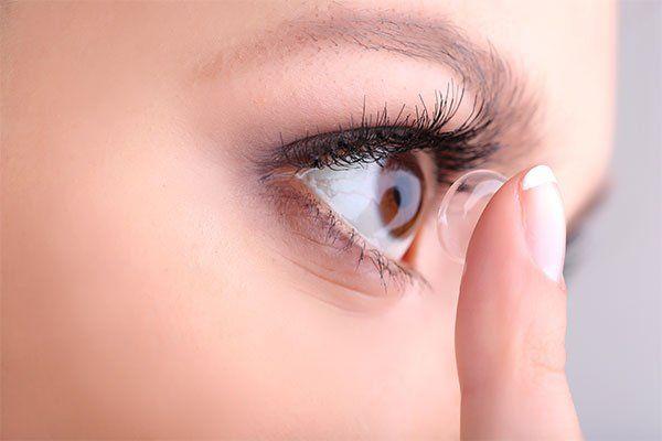 Giovane donna che mette una lente a contatto