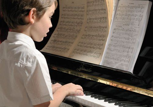 A little boy, playing the piano and reading sheet music