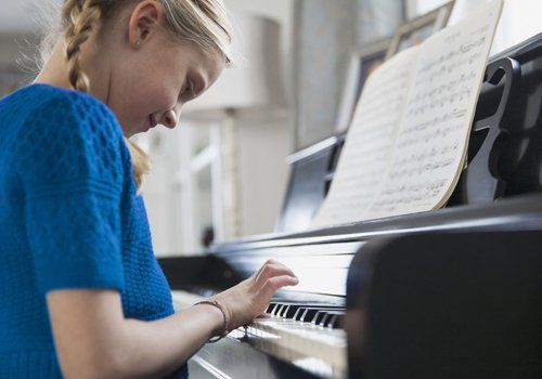 A little girl, smiling as she plays the piano