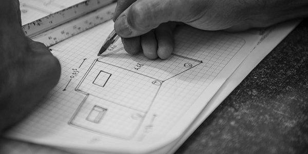 mano che disegna un progetto su un foglio a quadretti