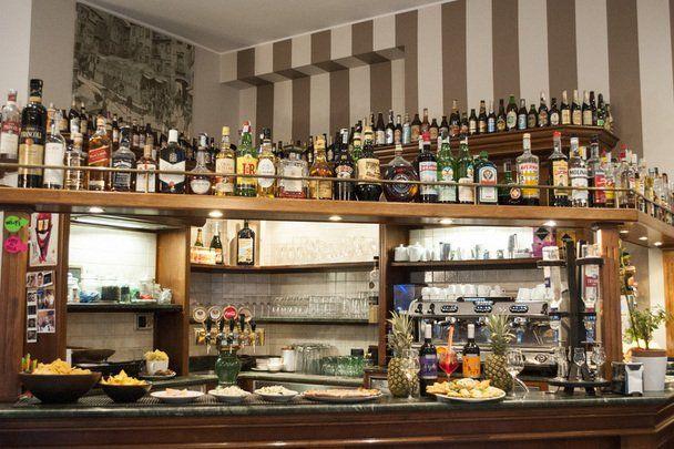 vista del bancone del bar  con dei piatti di salatini e le bottiglie di alcolici in esposizione