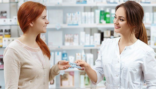 Attractive smiling pharmacist giving her client pills
