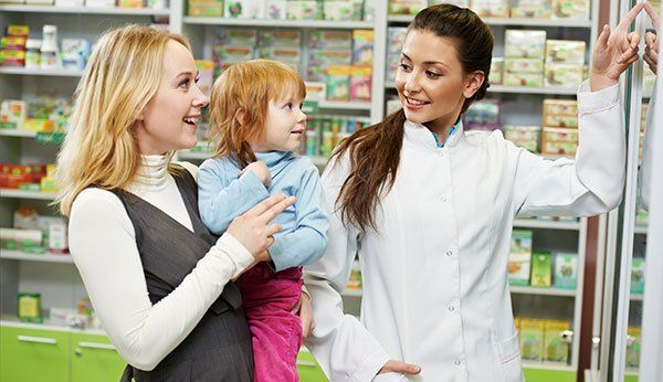 Cheerful pharmacist demonstrating vitamins to child girl