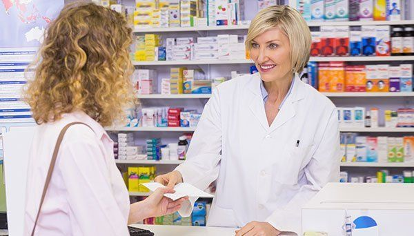 Customer handing a prescription to a smiling pharmacist in the pharmacy