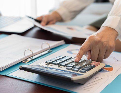 Un signore alla scrivania con calcolatrice, computer e quaderno ad anelli con fogli raffiguranti dei grafici