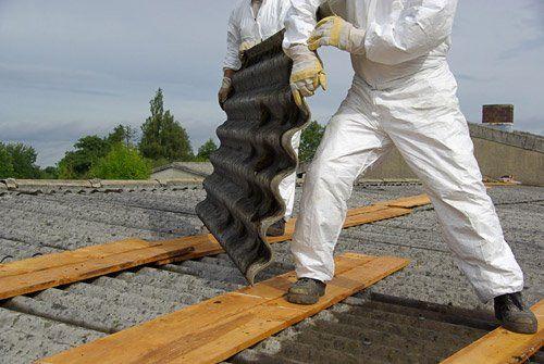 Due tecnici sollevano una lastra di amianto